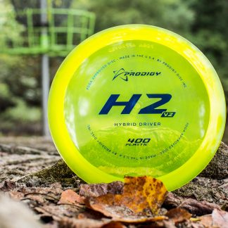 A beautiful yellow Prodigy H2 V2 sitting on the ground with a basket in the background.